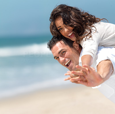 Buy stock photo Loving couple having fun on the beach, enjoying their summer holiday together.
