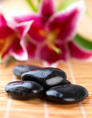 Buy stock photo Close up shot of several hot stones on a mat, from the beauty spa. With pink lilies in the background.