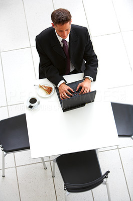 Buy stock photo High angle shot of businessman working on a laptop in an airport cafe