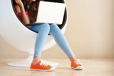 Buy stock photo Cropped view of girl sitting on an egg shaped chair using laptop