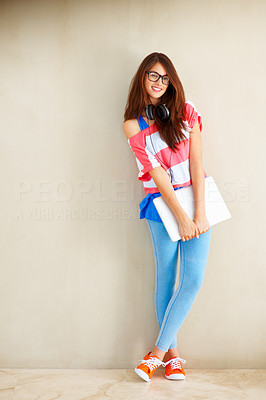 Buy stock photo Full length of an attractive young girl standing against wall with headphones and laptop
