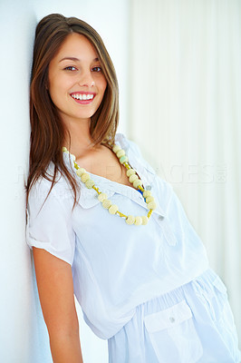 Buy stock photo Portrait of an attractive young woman leaning against wall and smiling