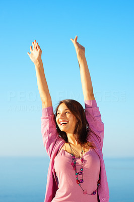 Buy stock photo Attractive young woman standing against sky with hands raised