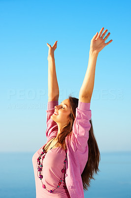 Buy stock photo Cute young woman standing against sky with hands raised