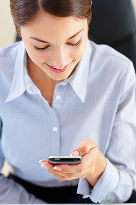 Buy stock photo Young businesswoman reading text message from her cellphone