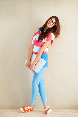 Buy stock photo Full length of an attractive young girl standing casually near wall and holding laptop