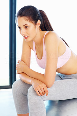 Buy stock photo Fit young woman sitting on pilates ball