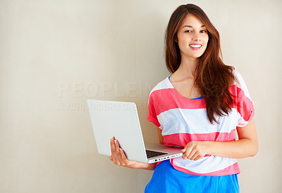 Buy stock photo Portrait of beautiful young woman standing near wall and using laptop