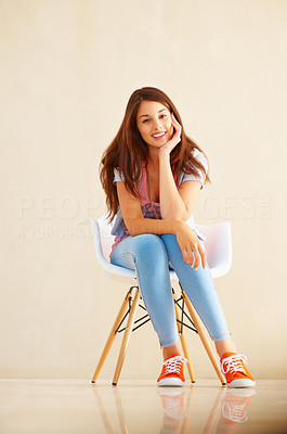 Buy stock photo Full length of young girl sitting casually on chair and giving you an attractive smile
