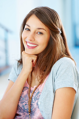 Buy stock photo Portrait of beautiful young woman sitting on chair with hand on chin and smiling