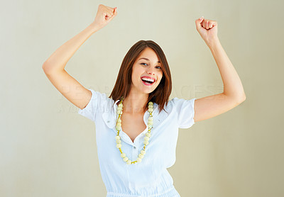 Buy stock photo Excited young girl with arms raised against plain background