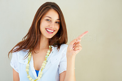 Buy stock photo Portrait of smiling young woman pointing at copyspace