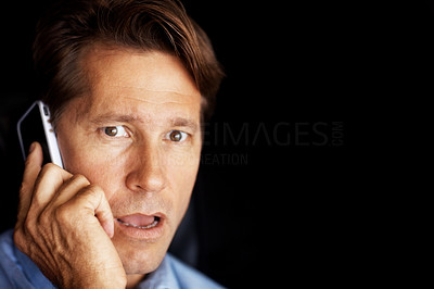 Buy stock photo Closeup portrait of a worried businessman speaking on cellphone against dark background