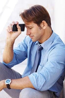 Buy stock photo Portrait of a thoughtful young male entrepreneur sitting near wall and holding cellphone