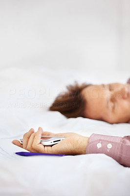 Buy stock photo Portrait of a tired businessman sleeping on bed with cellphone in hand at home