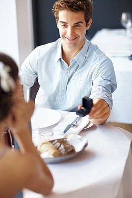 Buy stock photo Handsome young man romantically proposing to girlfriend and offering engagement ring at a restaurant
