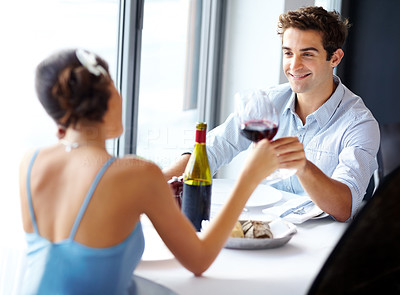 Buy stock photo Young happy amorous couple celebrating with red wine at restaurant
