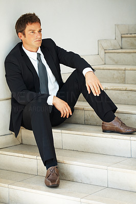 Buy stock photo Businessman sitting on steps, looking off into distance
