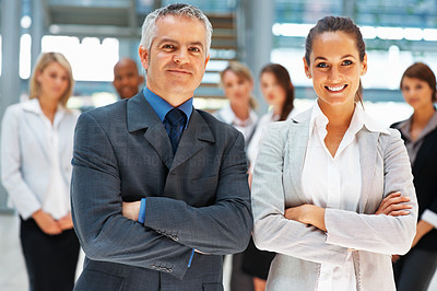 Buy stock photo Confident man and woman executives with colleagues in background
