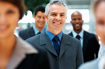 Buy stock photo Focus on smiling businessman with team in background