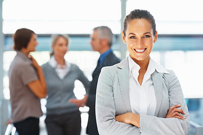 Buy stock photo Businesswoman smiling with arms crossed, colleagues in background