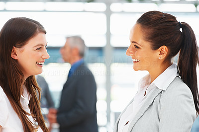 Buy stock photo Two female executives having discussion with colleagues in background