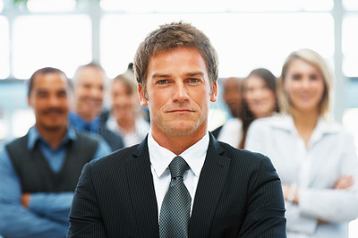 Buy stock photo Handsome executive with serious expression and colleagues in background