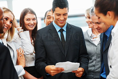Buy stock photo Business man looking at paperwork while surrounded by peers