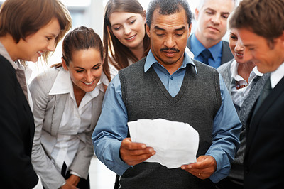 Buy stock photo Group of colleagues watching colleague read report
