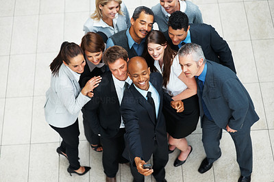 Buy stock photo Colleagues posing while executive takes photo with mobile