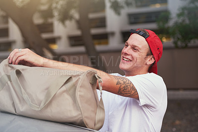 Buy stock photo Shot of a young man opening his tog bag