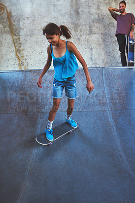 Buy stock photo Shot of a young woman doing tricks on her skateboard at the skatepark
