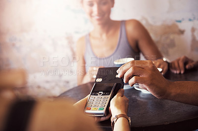 Buy stock photo Cropped shot of a customer paying for coffee with a credit card at a cafe