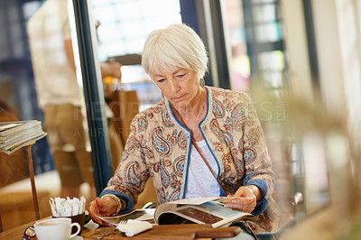 Buy stock photo Shot of a senior woman reading a magazine in a cafe