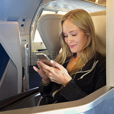 Buy stock photo Shot of a young woman using her cellphone while sitting in first class in an airplane