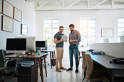 Buy stock photo Shot of two creative businessmen talking together over a tablet while standing in their office