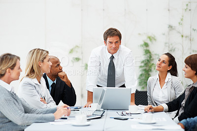 Buy stock photo Executive at head of table commanding attention from colleagues