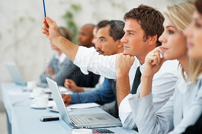 Buy stock photo Focus on business man with hand raised during a meeting with colleagues on either side