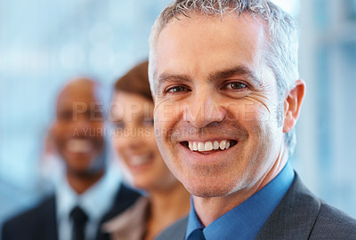 Buy stock photo Closeup of mature business man smiling with colleagues in background
