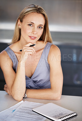 Buy stock photo Portrait of a beautiful young businesswoman sitting by her desk holding a pen