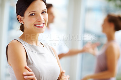 Buy stock photo Portrait of a confident young businesswoman smiling at you, with colleagues in the background - copyspace