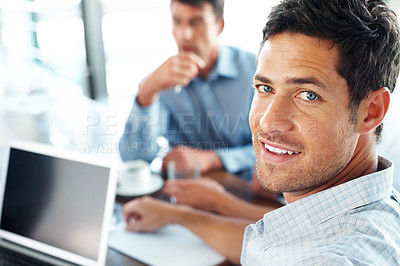 Buy stock photo Smiling satisfied businessman looking at you with his colleagues in the background during a meeting in the office