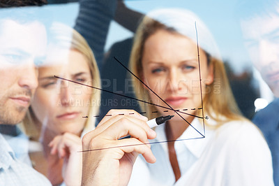 Buy stock photo Young businessman drawing a diagram on a transparent board while his colleagues look on