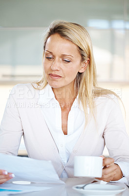 Buy stock photo Portrait of a pretty young businesswoman reading a document while drinking coffee