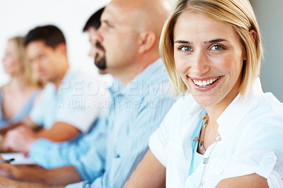 Buy stock photo Closeup of an attractive young business woman smiling in a conference with her colleagues