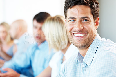 Buy stock photo Handsome young businessman smiling in a conference with his associates in background