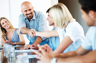 Buy stock photo Successful business colleagues shaking hands with each other in a meeting at office