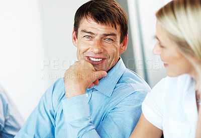 Buy stock photo Closeup of a handsome mature businessman discussing with his colleague during meeting at office