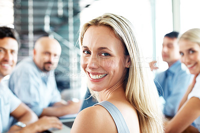 Buy stock photo Portrait of a young businesswoman attending a conference with rest of her team at office