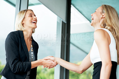 Buy stock photo Portrait of a smiliing young businesswoman shaking hand with a woman in her office